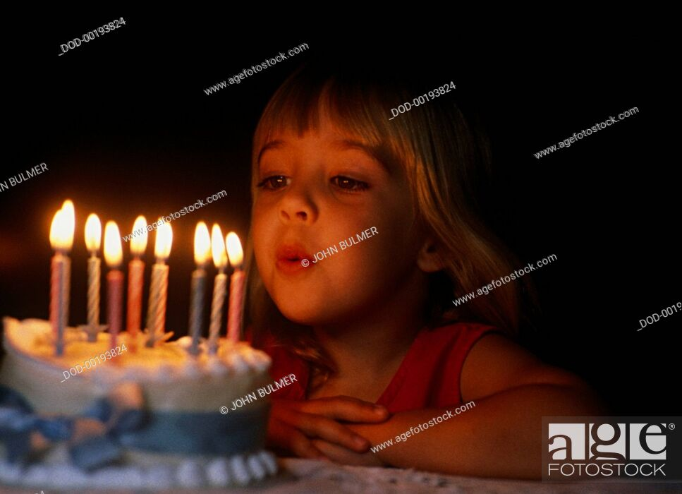 Imagen: Young girl bowing out candles on birthday cake in dark light.