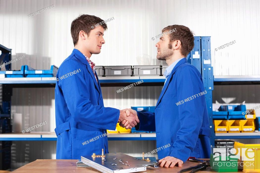 Stock Photo: Germany, Neukirch, Apprentice and instructor shaking hands, side view, portrait.