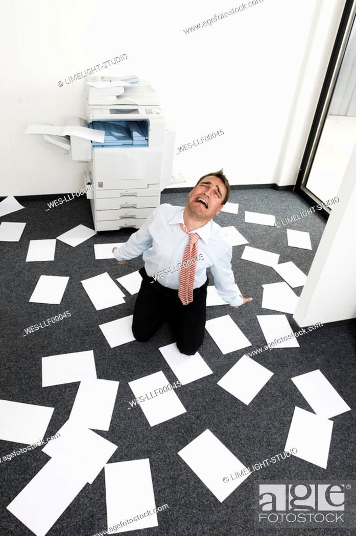 Stock Photo: Businessman kneeling among slips of paper, looking desperate, elevated view.
