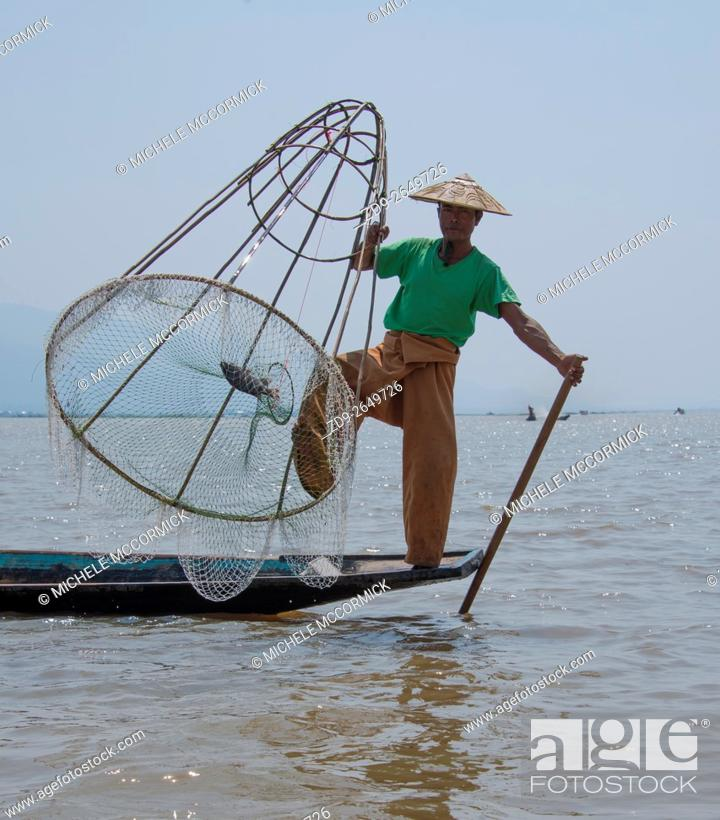 Stock Photo: A fisherman poses for tourists on Inle Lake.