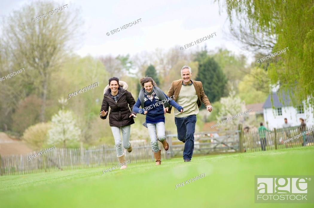 Stock Photo: Happy family running in a field.