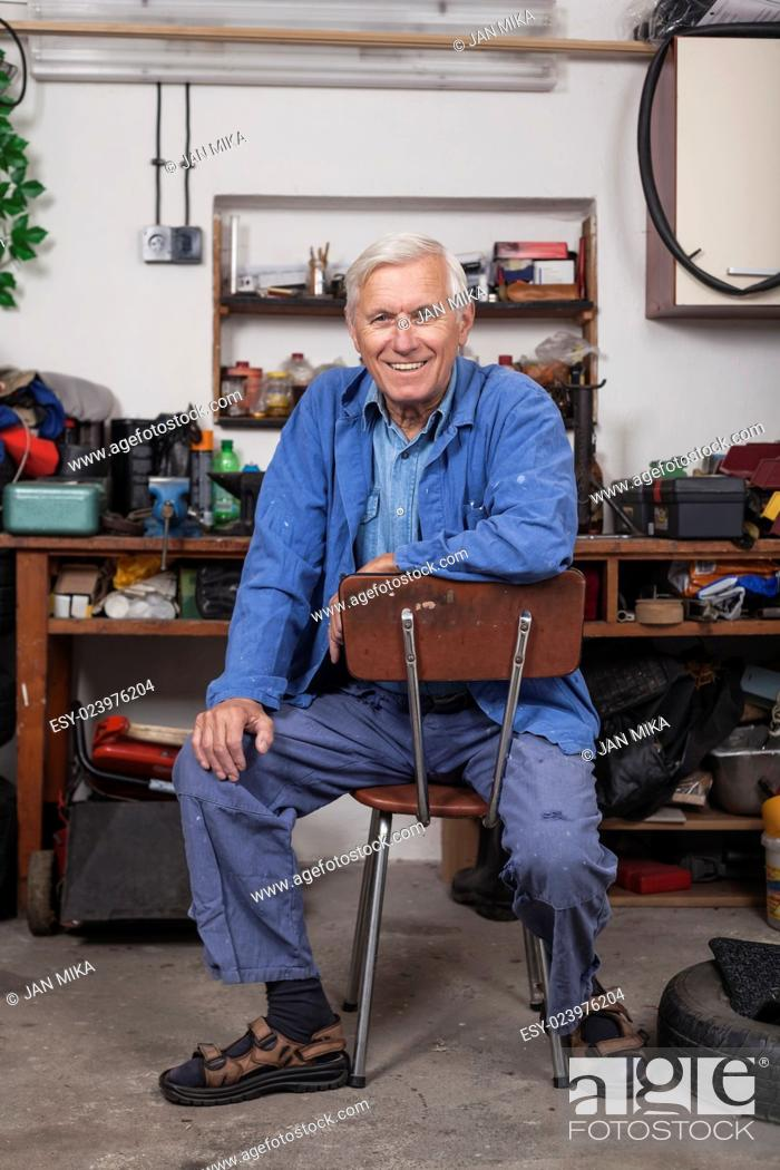 Stock Photo: Portrait of happy senior worker sitting in his workshop.