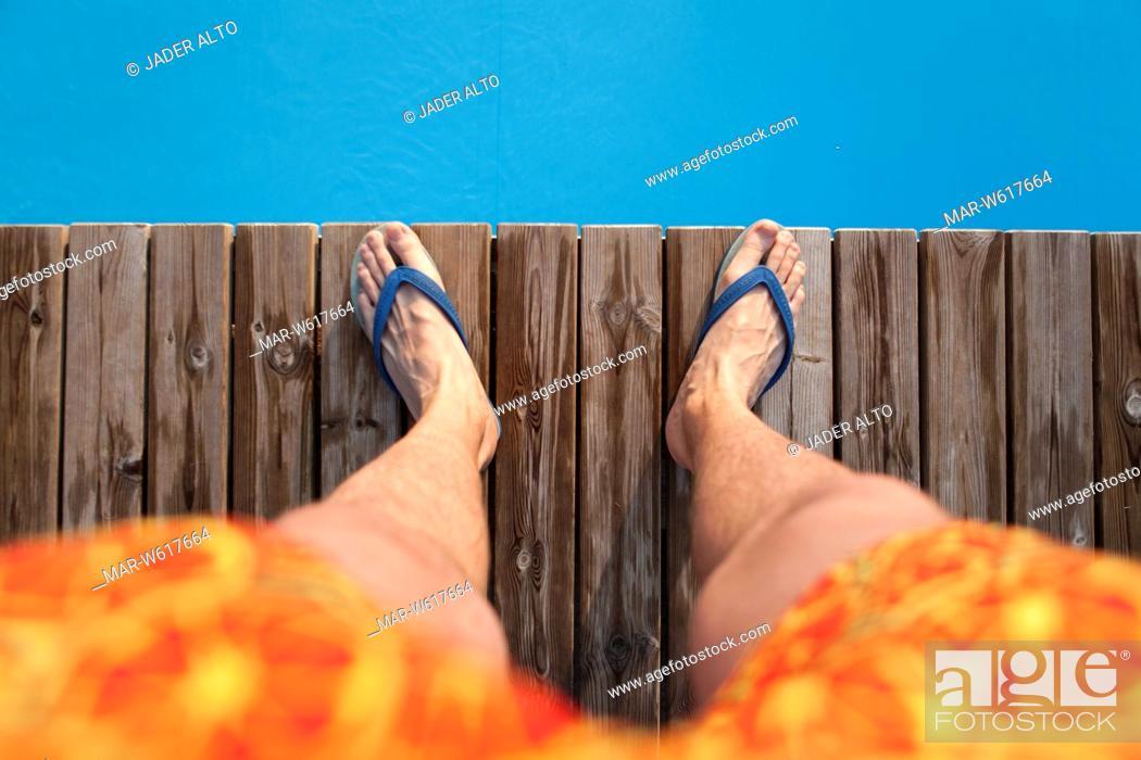 Stock Photo: gambe di un uomo in costume sul bordo di una piscina.