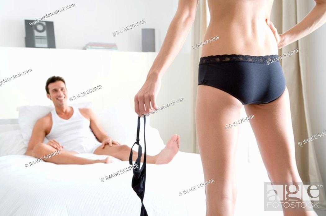 Stock Photo: Woman undressing for man.