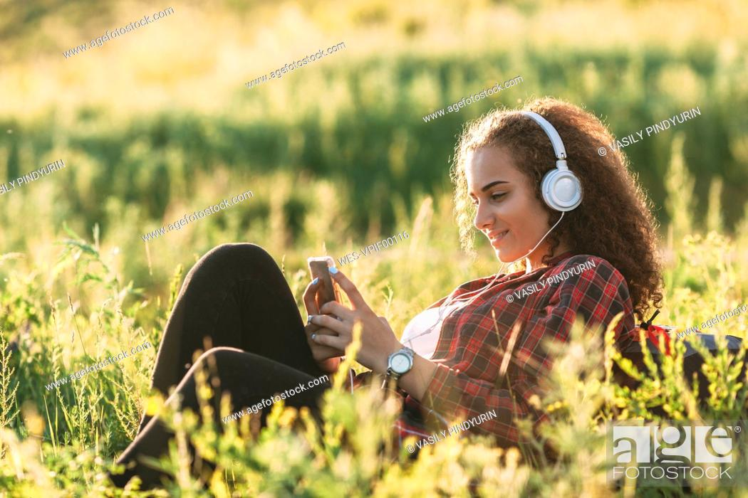 Imagen: Teenage girl listening music with headphones on a meadow looking at cell phone.