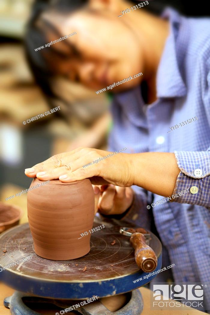 Stock Photo: Asian woman moulding clay on a pottery wheel.