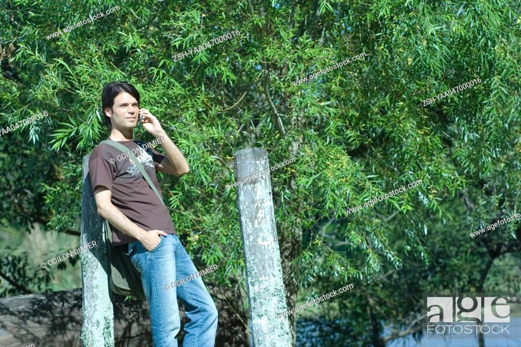 Stock Photo: Casual man leaning against post, using cell phone.