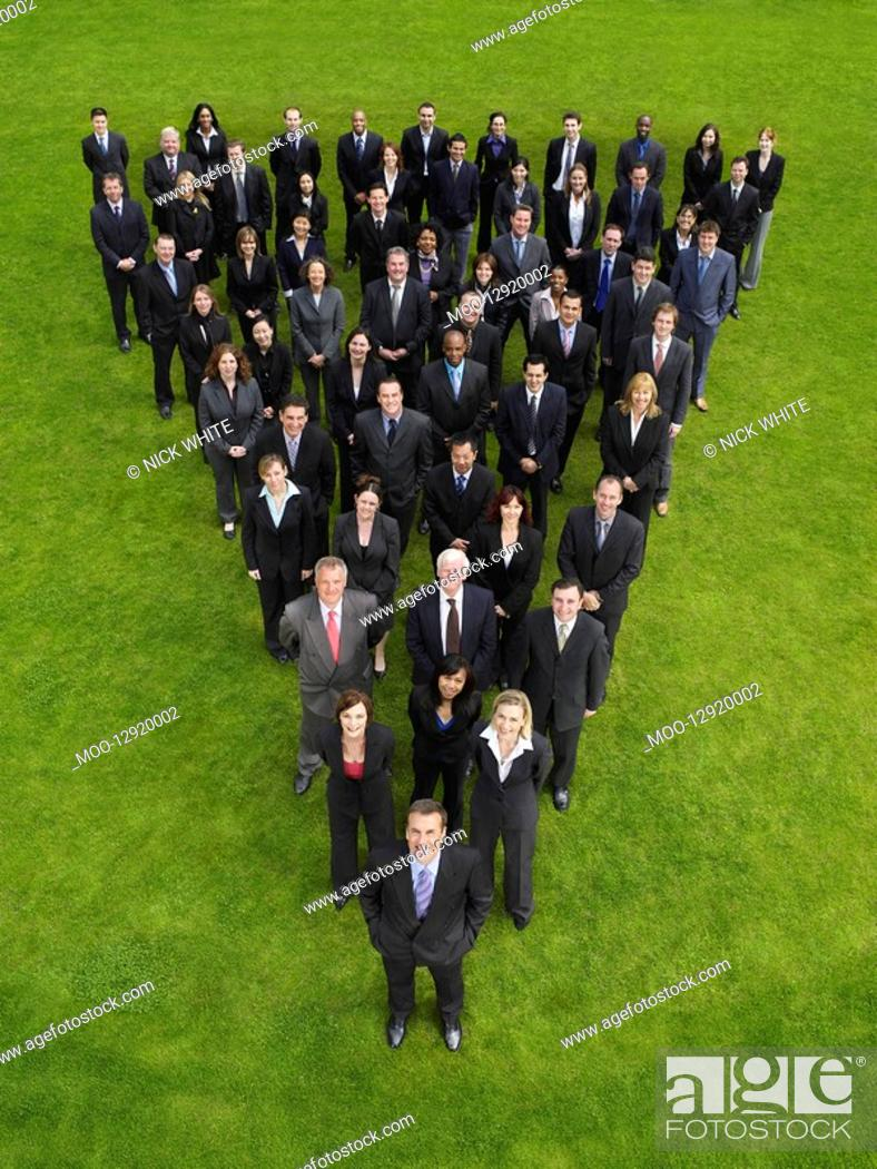 Stock Photo: Large group of business people standing in triangle formation elevated view.