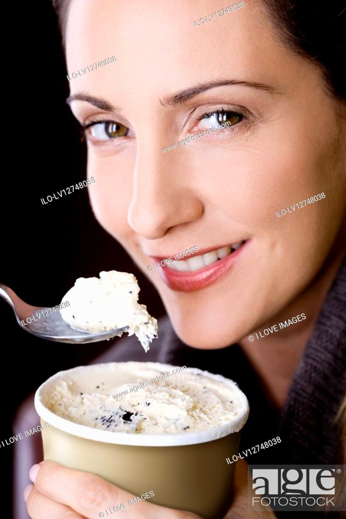 Stock Photo: A mid adult woman eating ice cream, close-up.