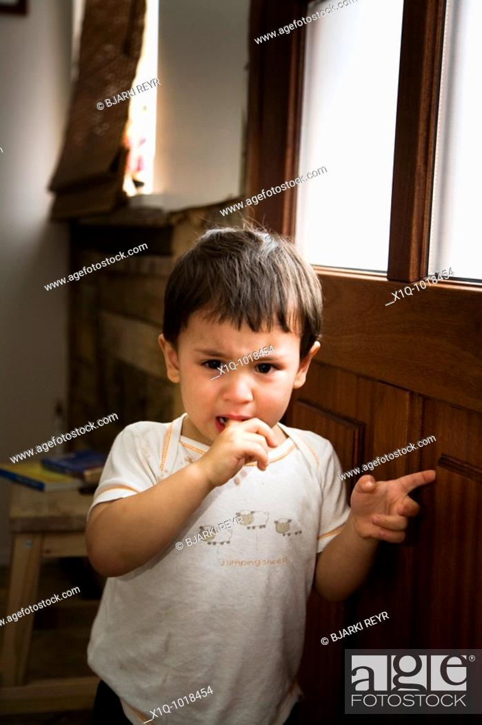 Stock Photo: Young boy waiting by the door at home, crying  Iceland.