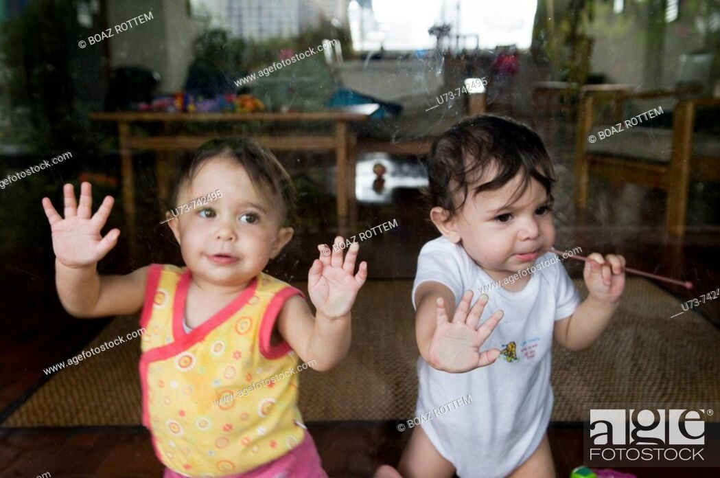 Stock Photo: Cute 1 year old twins play by the window.