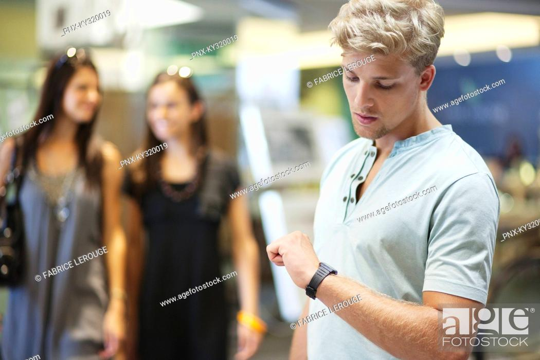 Stock Photo: Young man checking the time with two women in the background at a clothing store.