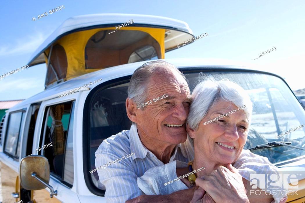 Stock Photo: Senior couple embracing by camper van, smiling.
