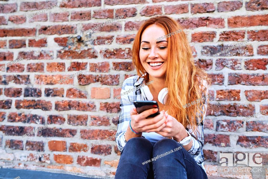 Stock Photo: Cheerful young woman sitting against brick wall and using smartphone.