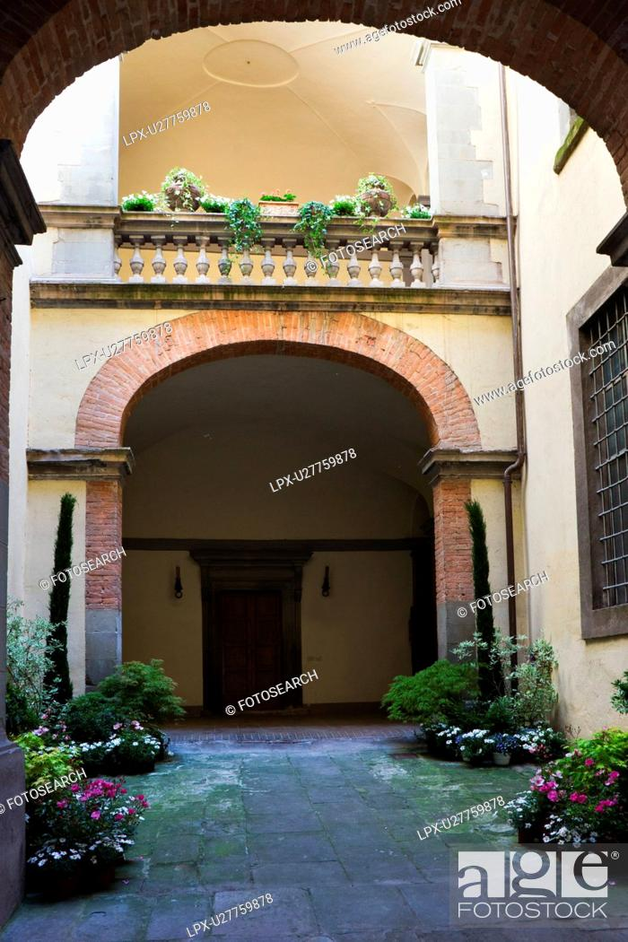 Stock Photo: Detail of inner courtyard of Italian Renaissance palazzo, decorated with flowers, with arched windows and balustrade, brick and stucco, Todi, Umbria.