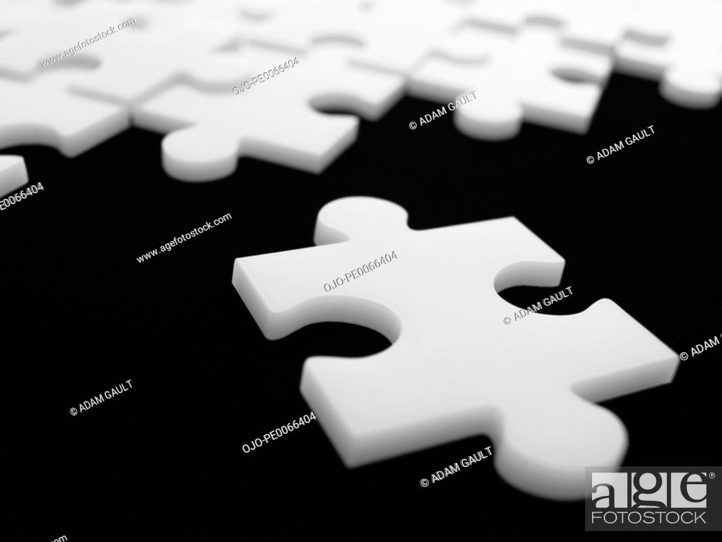 Stock Photo: Close up of single puzzle piece near others.