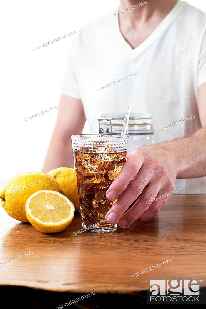 Imagen: Man Grabbing Glass of Iced Tea from Wood Table.