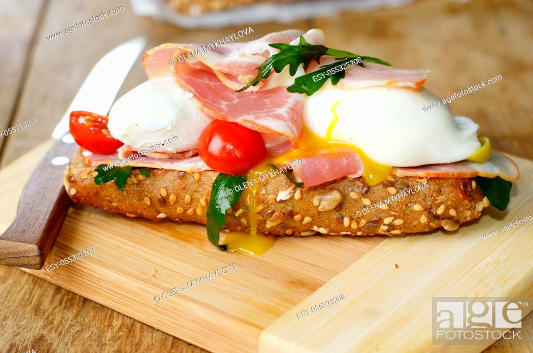 Stock Photo: Bacon and poached eggs sandwich on the cut board.