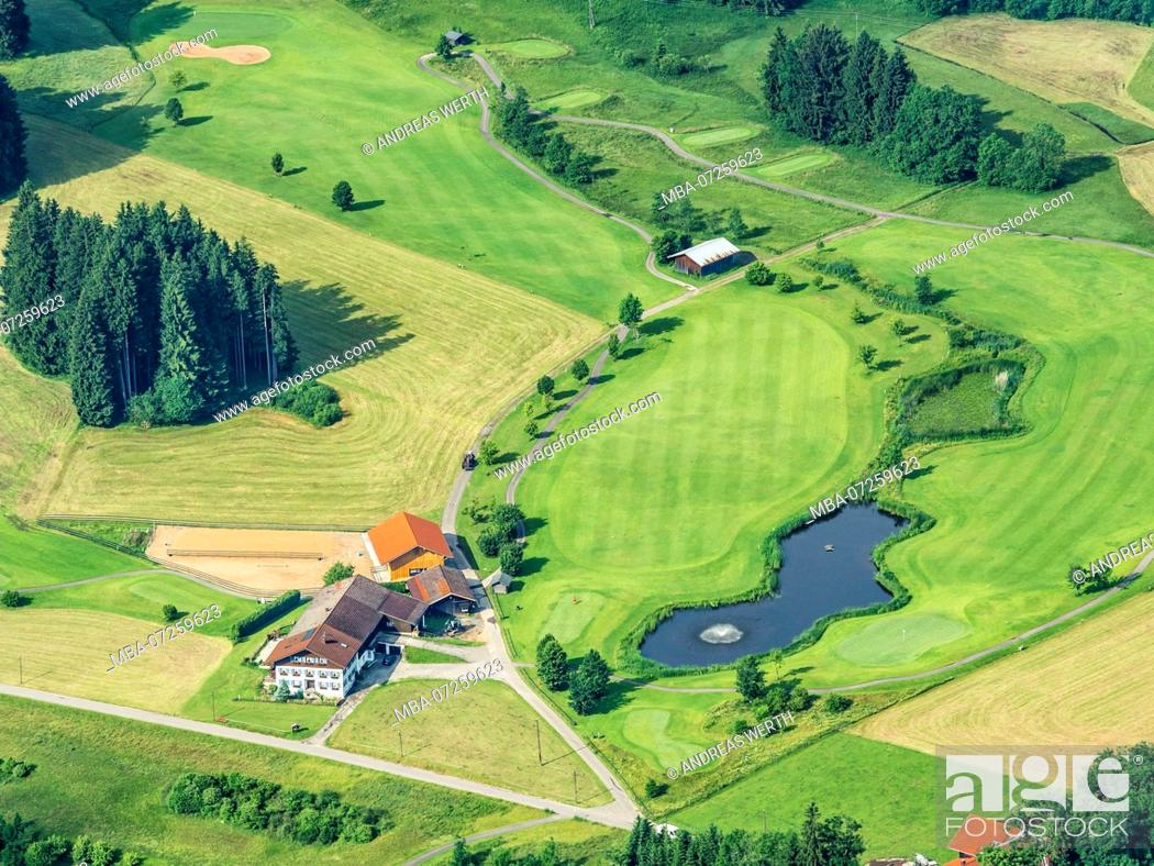 Stock Photo: Lonely farm house surrounded by meadows, lake with fountain, small golf course, aerial view, slope of bavarian alps near Oberstdorf, Allgäu, Allgaeu, Bavaria.