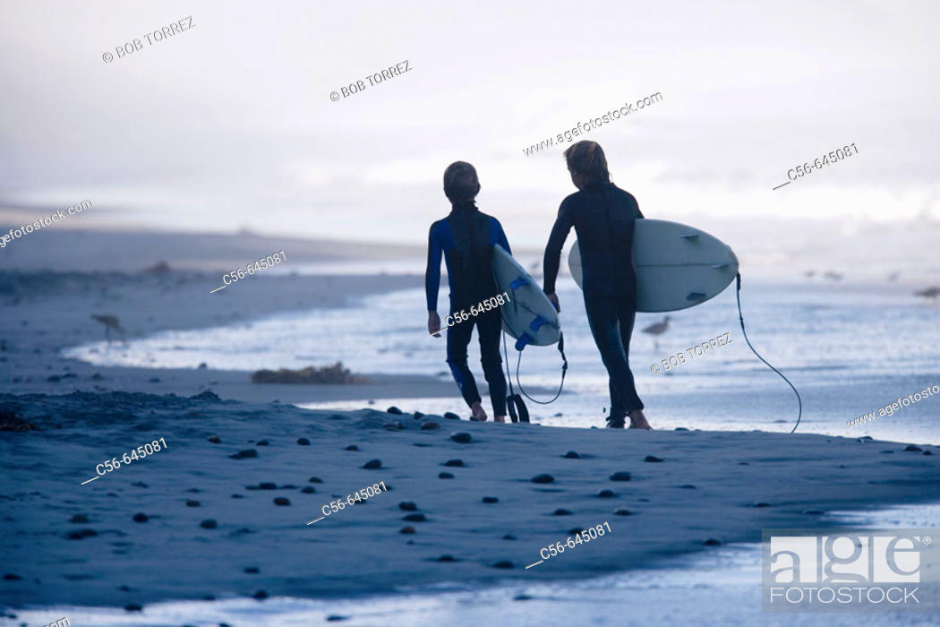 Stock Photo: Two young boys walking down and sand and pebblestone beach carrying there surfboards.