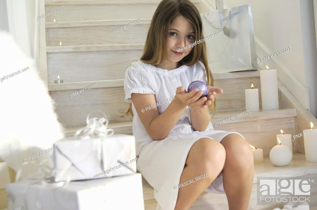 Stock Photo: Little girl sitting indoors, holding a Christmas ball, indoors.