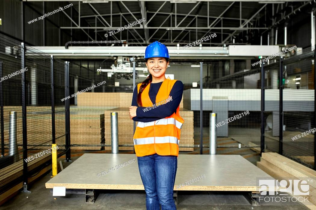 Stock Photo: Portrait of smiling female worker in factory warehouse.