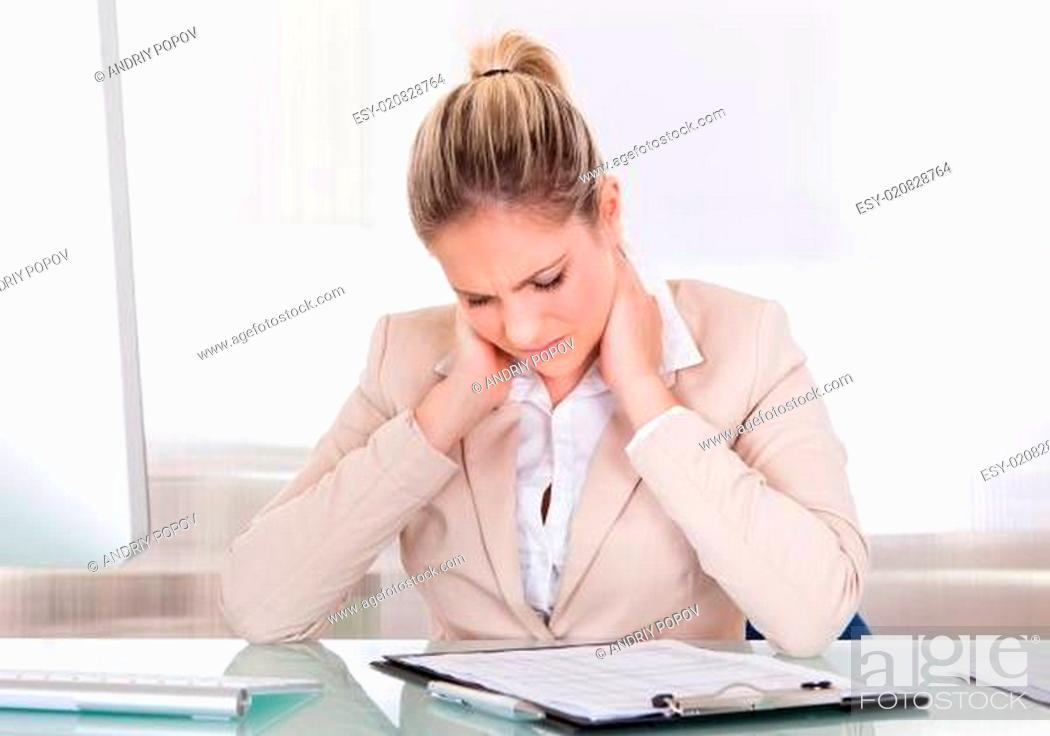Stock Photo: Young Businesswoman Suffering From Neck Pain At Office.