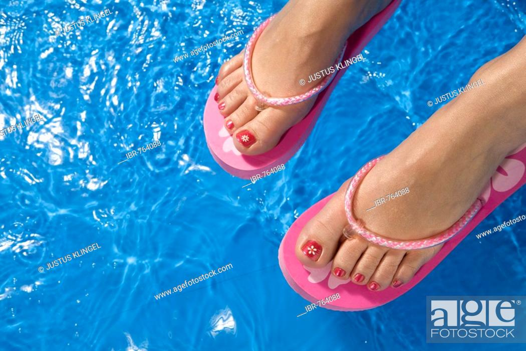 7cb6456006d70 Stock Photo - Feet wearing flip-flops dangling over the side of a paddling  pool