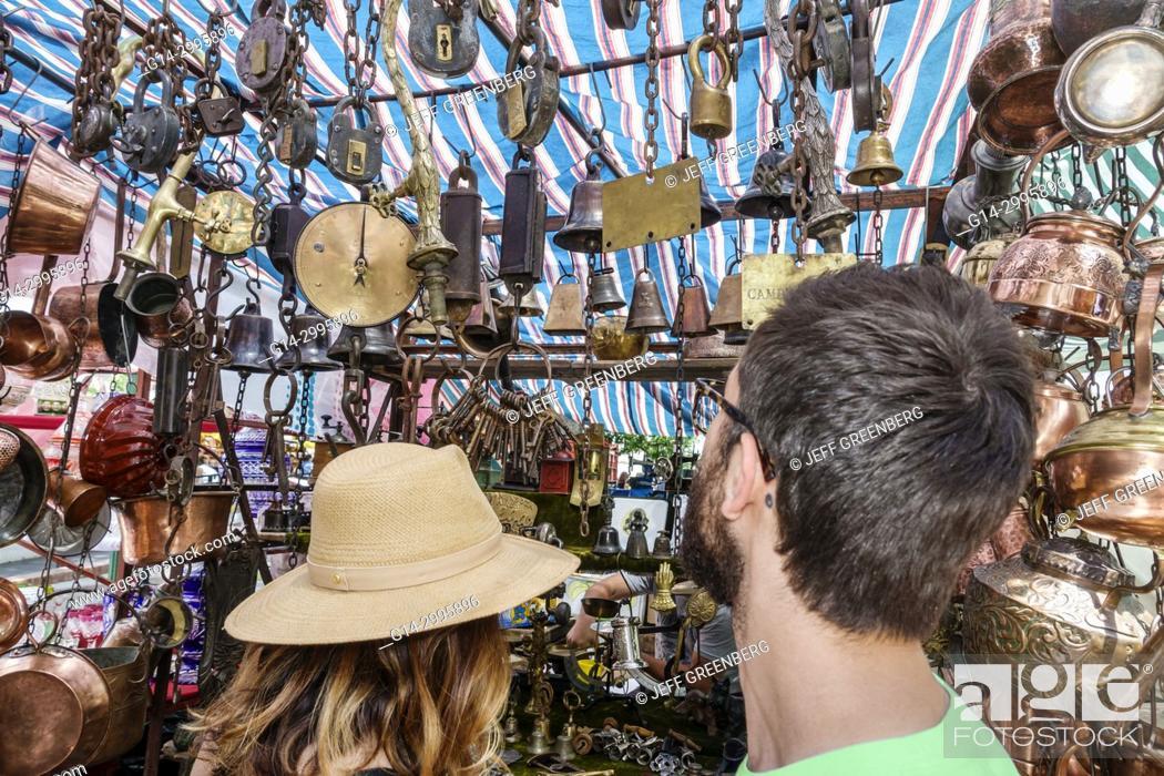 Stock Photo: Argentina, Buenos Aires, San Telmo Plaza Dorrego, art fair, antiques, marketplace vendors vendor booths stalls, shopping, bells, copper, man, woman, couple.