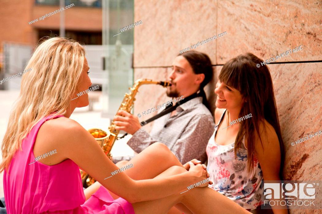 Stock Photo: Man playing the saxophone to women, Osijek, Croatia.