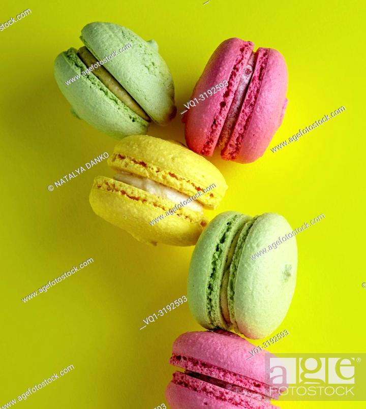 Imagen: multicolored round almond meal meringue pastries macarons on a bright yellow background, close up.
