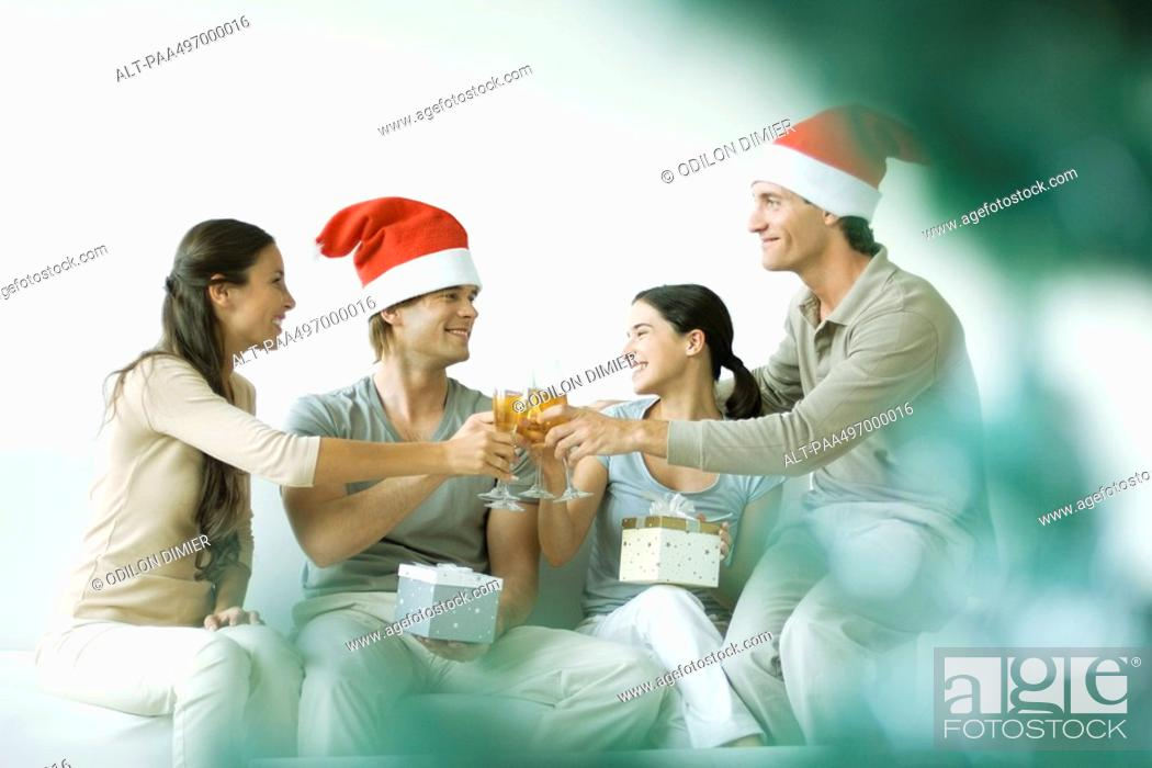 Stock Photo: Two couples toasting and exchanging gifts, men wearing Santa hats.