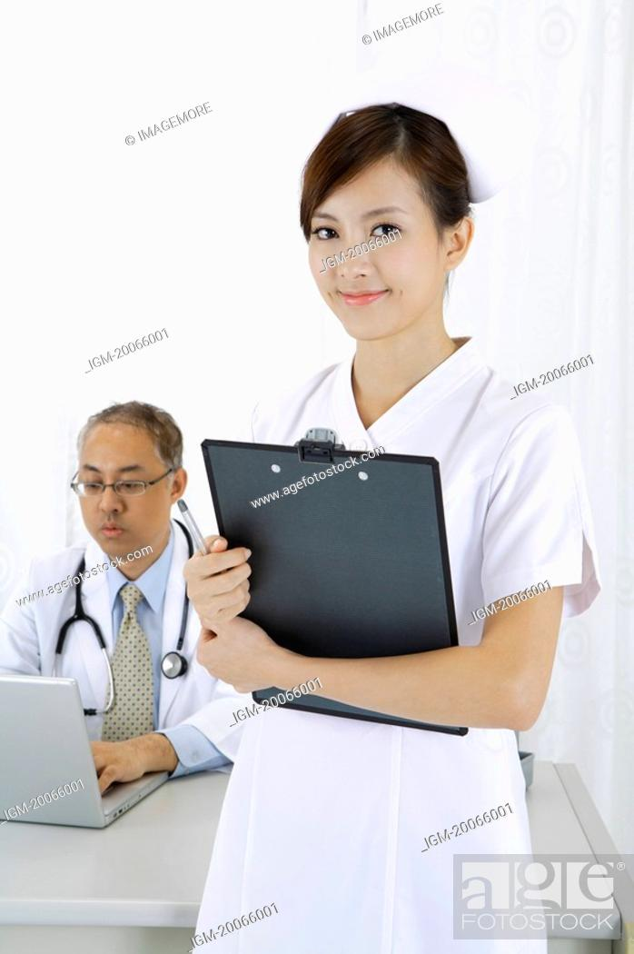 Stock Photo: Young nurse standing near doctor and smiling.