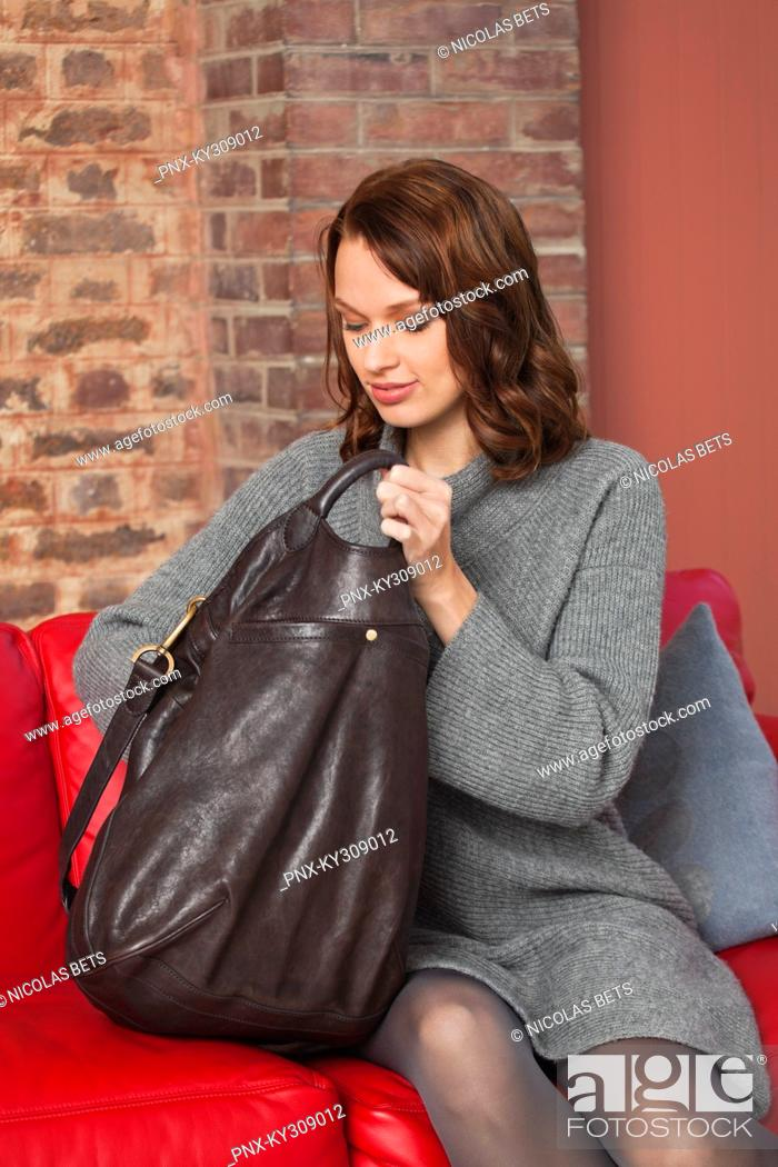 Stock Photo: Young woman searching in her purse.
