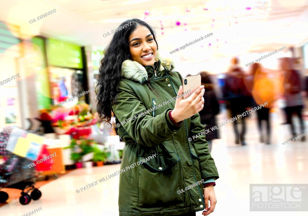Stock Photo: Young woman taking selfie in shopping mall.