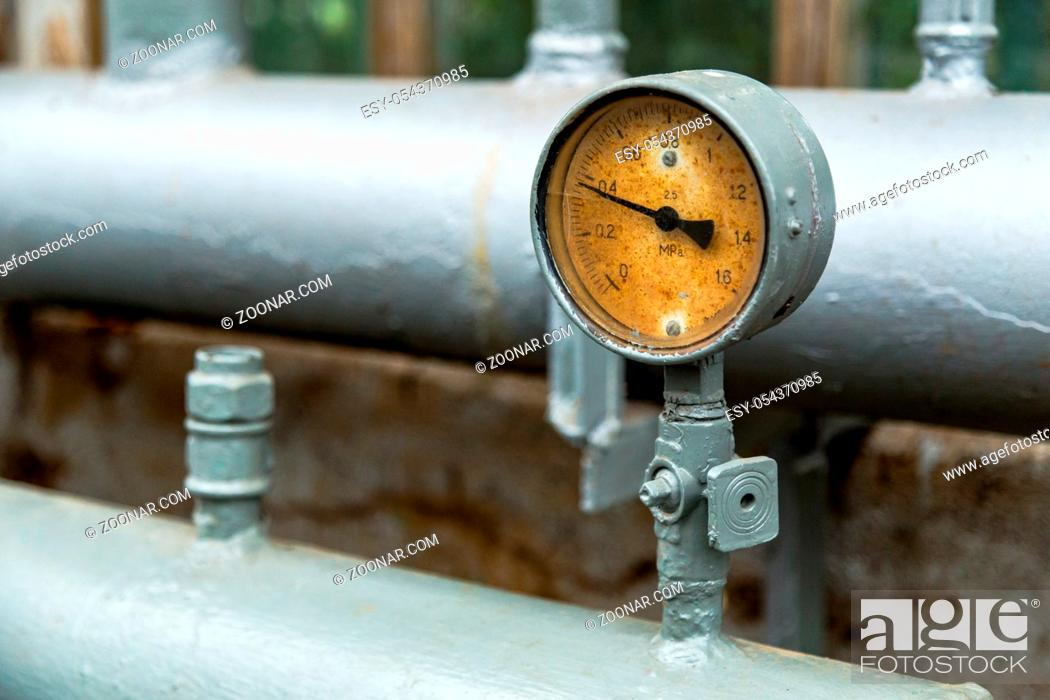 Stock Photo: gauge pressure in the pipeline, a wall in the background.