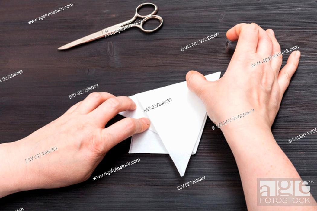 Stock Photo: top view of female hands fold sheet of paper to make figure on dark brown wooden table.