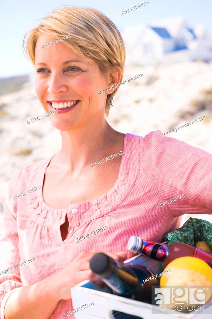 Stock Photo: Woman carrying a crate on the beach.