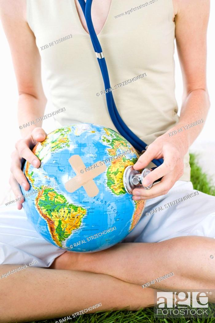 Stock Photo: young woman examinating globe.