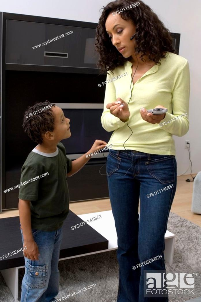 Stock Photo: Portrait of a boy bothering his mom who is busy.