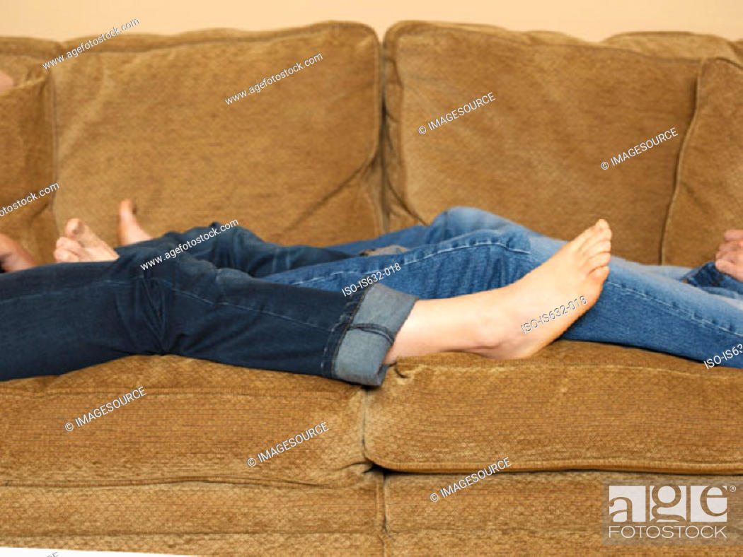 Stock Photo: Couple reclining on sofa.