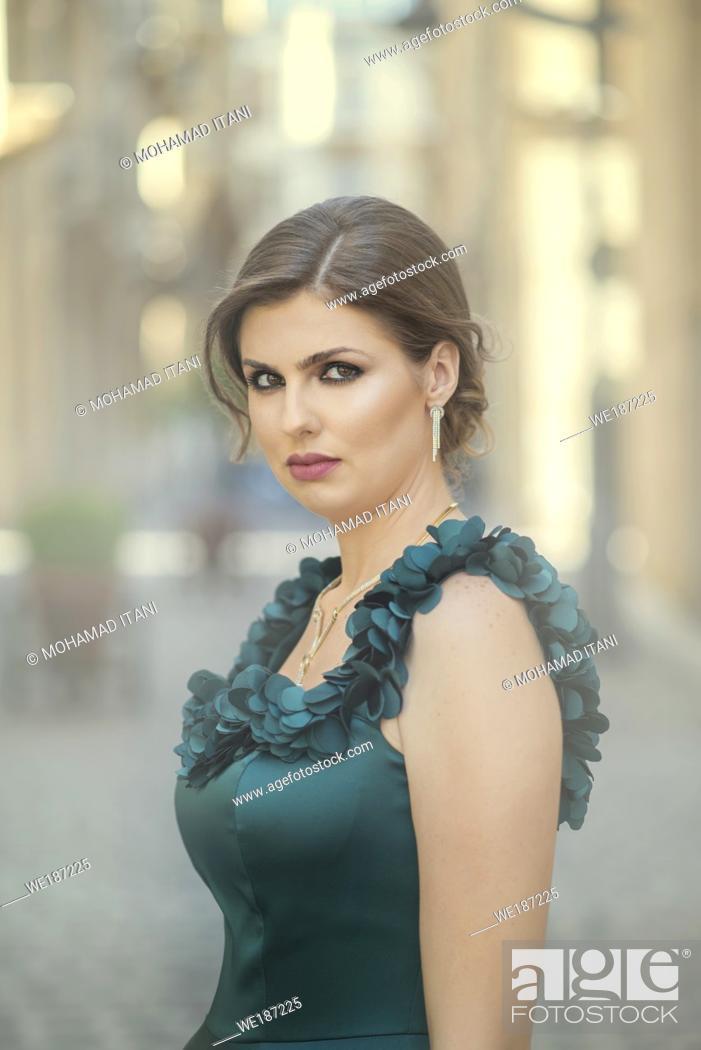 Stock Photo: Beautiful woman looking at camera outdoors.