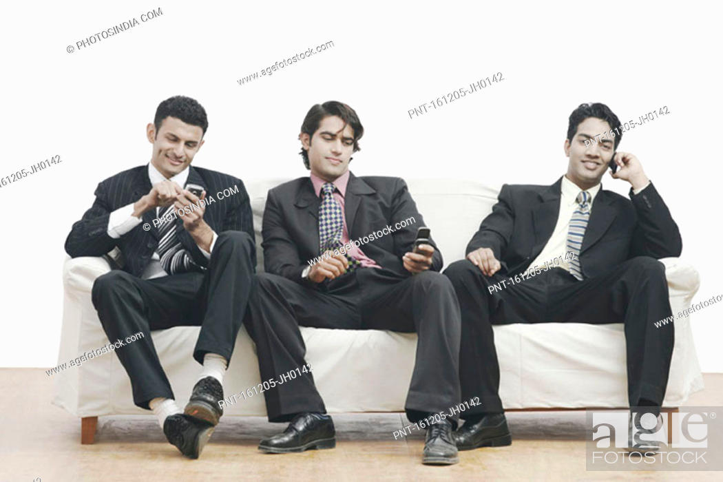 Stock Photo: Three businessmen sitting on a couch holding mobile phones.
