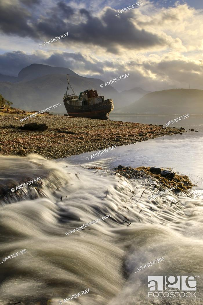 Stock Photo: A waterfall and abandoned boat at Corpach in Scotland with Ben Nevis in the distance.