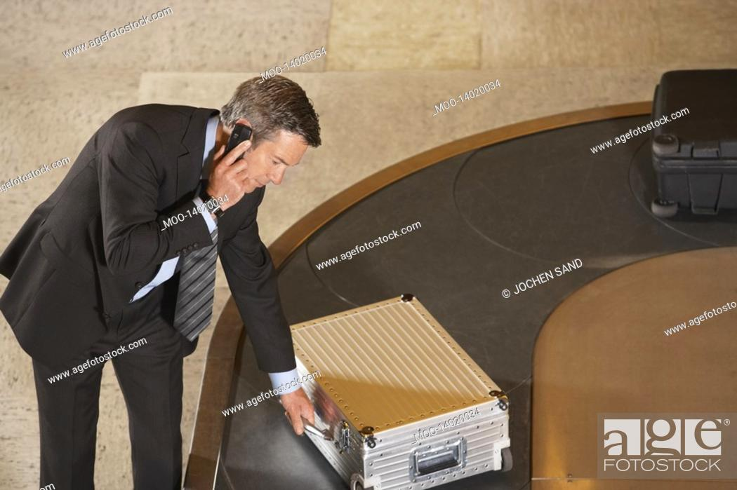 Stock Photo: Business man claiming suitcase at luggage carousel in airport.