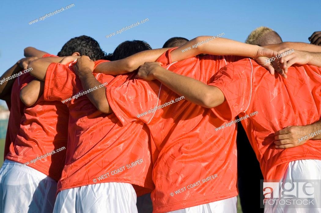 Stock Photo: Soccer team in huddle back view.