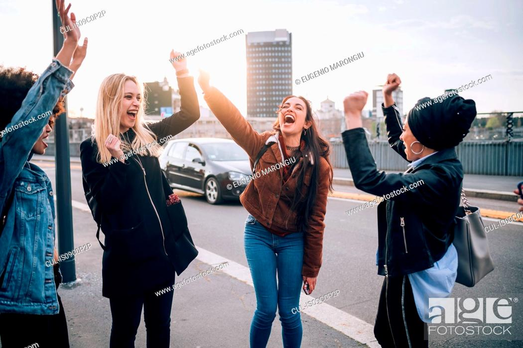 Stock Photo: Friends raising arms in triumph in street, Milan, Italy.