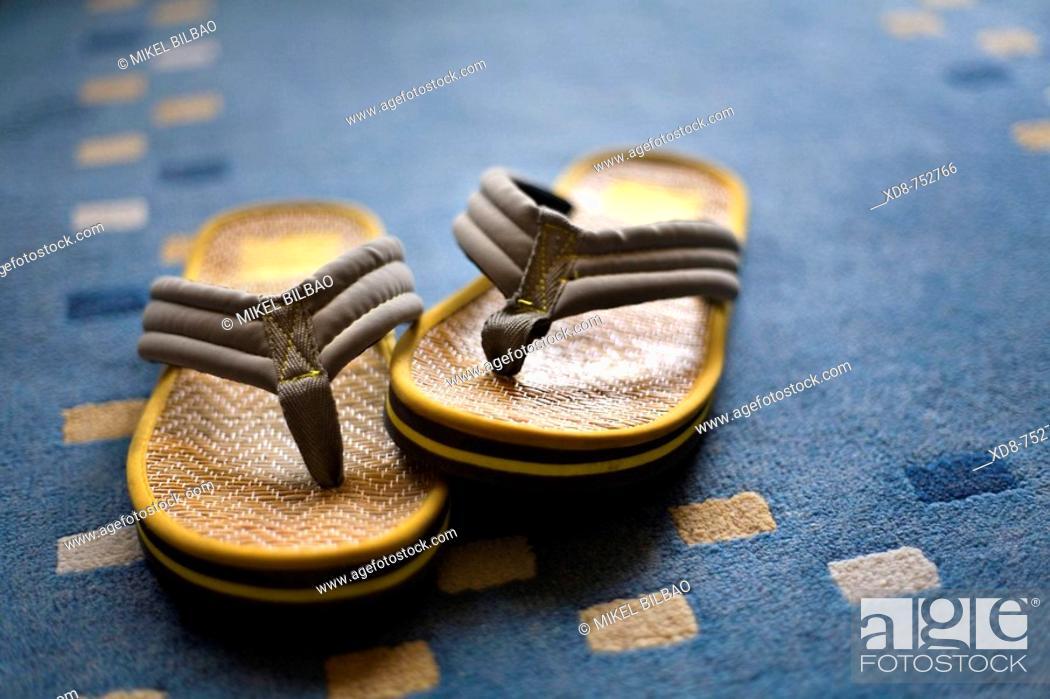 Stock Photo: Sandal pair over a carpet.