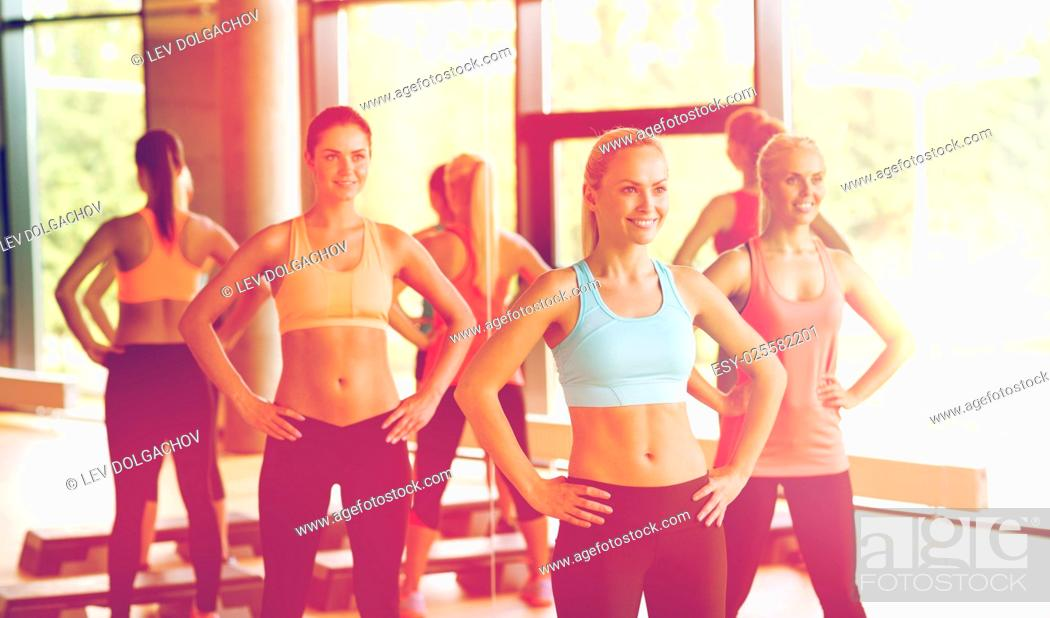Stock Photo: fitness, sport, training, gym and lifestyle concept - group of women working out in gym.