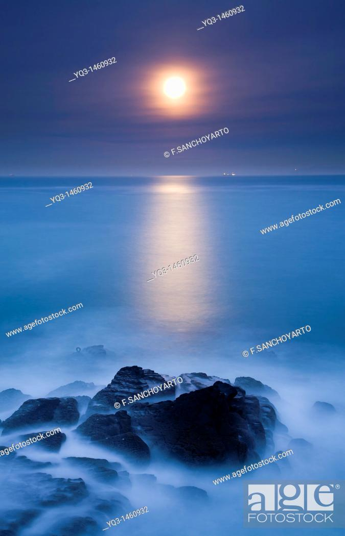 Stock Photo: Night view of the moon rising over the sea.